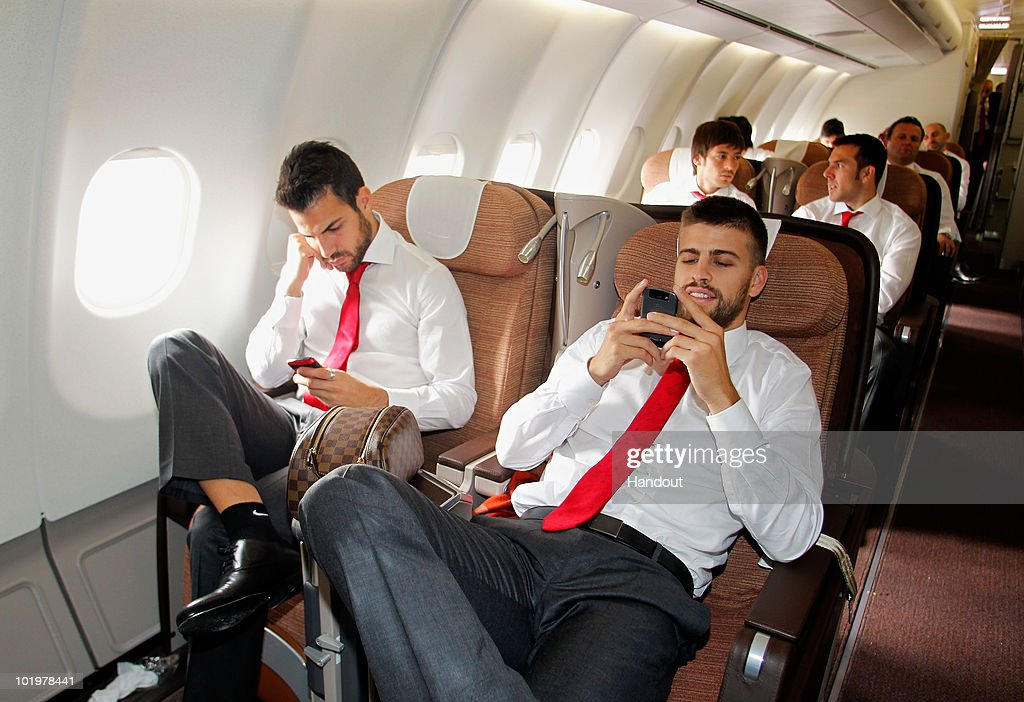 Gerard Pique (R) and Cesc Fabregas of Spain check their messages shortly after touch down at Johannesburg airport on June 11, 2010 in Johannesburg, South Africa.