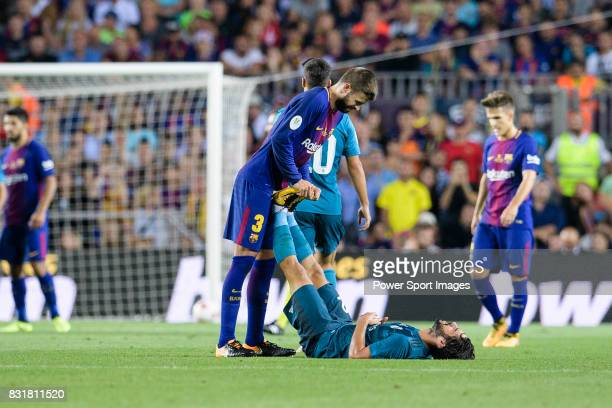 Gerard Pique Bernabeu of FC Barcelona helps Isco Alarcon of Real Madrid during the Supercopa de Espana Final 1st Leg match between FC Barcelona and...