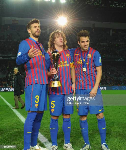 Gerard Pique Carles Puyol and Cesc Fabregas of Beacelona celebrate victory in the FIFA Club World Cup Final match between Santos and FC Barcelona at...