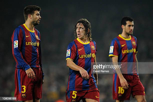 Gerard Pique Carles Puyol and Sergio Busquets of FC Barcelona look on during the La Liga match between FC Barcelona and Malaga at Nou Camp on January...