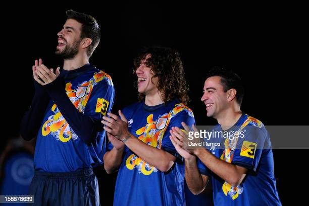 Gerard Pique Carles Puyol and Xavi Hernandez of Catalonia smile and appluad prior to a friendly match between Catalonia and Nigeria at CornellaEl...