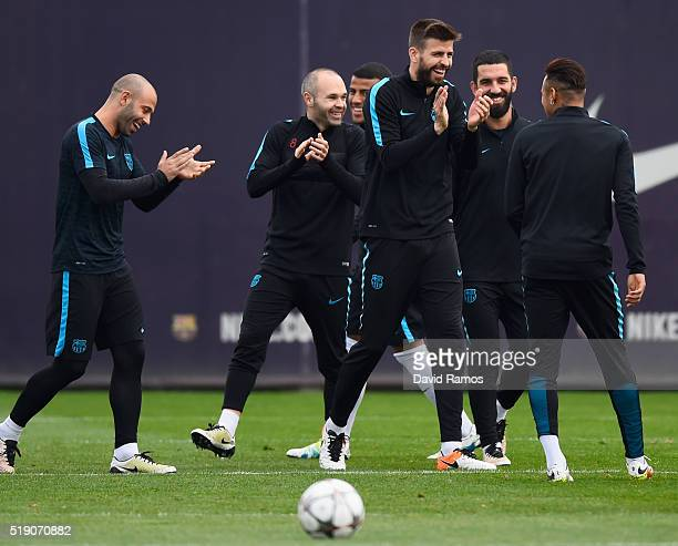 Gerard Pique laughs with team mates during a Barcelona training session ahead of their UEFA Champions League quarter final first leg match against...