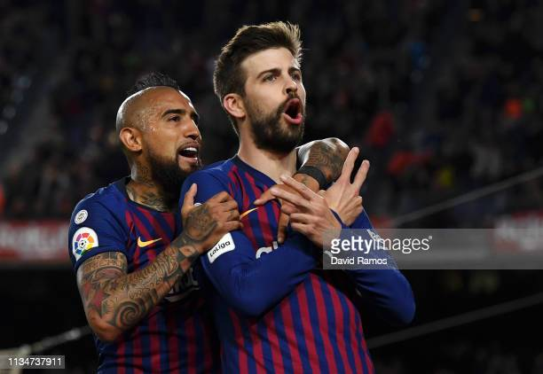 Gerard Pique of Barcelona celebrates after scoring his team's first goal with teammate Arturo Vidal during the La Liga match between FC Barcelona and...
