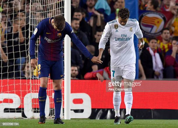 Gerard Pique of Barcelona checks on Cristiano Ronaldo of Real Madrid as he is injured as he scores his sides first goal during the La Liga match...