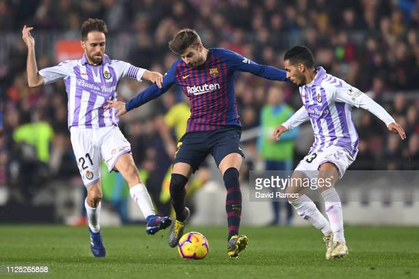 Gerard Pique of Barcelona is challenged by Michel of Real Valladolid and Anuar of Real Valladolid during the La Liga match between FC Barcelona and...