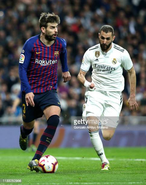 Gerard Pique of Barcelona is closed down by Karim Benzema of Real Madrid during the La Liga match between Real Madrid CF and FC Barcelona at Estadio...