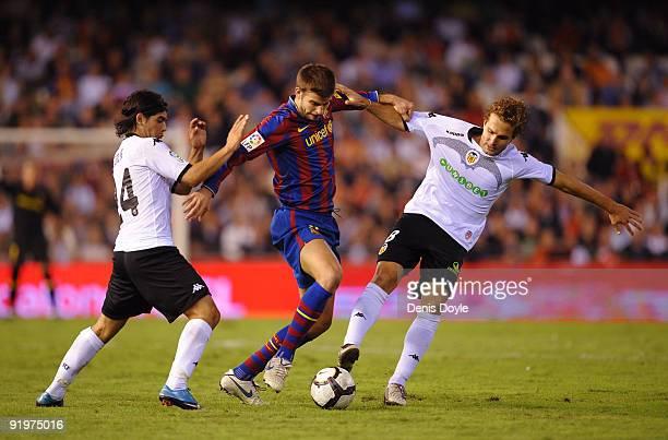 Gerard Pique of Barcelona is tackled by Ruben Baraja and Ever Banega of Valencia during the La Liga Match between Valencia and Barcelona at Estadio...
