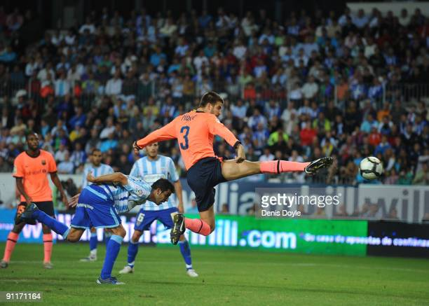 Gerard Pique of Barcelona scores his team's second goal during the La Liga match between Malaga and Barcelona at La Rosaleda Stadium on September 26...