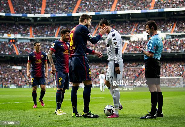 Gerard Pique of Barcelona taps Cristiano Ronaldo of Real Madrid on his cheek after referee Miguel Perez fined Pique with a yellow card for fouling...