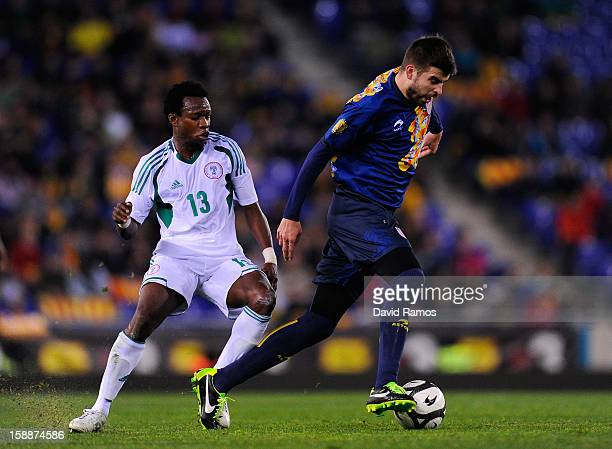 Gerard Pique of Catalonia duels for the ball with Emenike Emmanuel of Nigeria during a friendly match between Catalonia and Nigeria at CornellaEl...