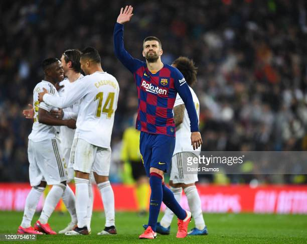 Gerard Pique of FC Barcelona acknowledges his supporters as Real Madrid CF players celebrate following their victory during the Liga match between...