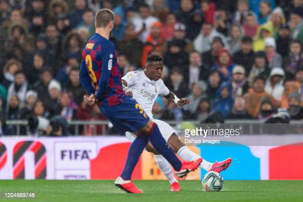 Gerard Pique of FC Barcelona and Vinicius Jr of Real Madrid battle for the ball during the Liga match between Real Madrid CF and FC Barcelona at...