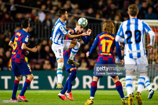 Gerard Pique of FC Barcelona battles for the ball with Mikel Merino of Real Sociedad during the Liga match between FC Barcelona and Real Sociedad at...