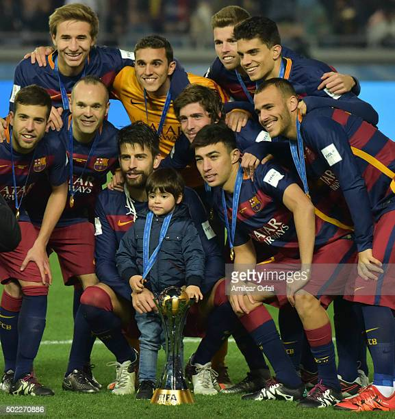 Gerard Pique of FC Barcelona celebrates with his son and teammates holding the trophy after the FIFA Club World Cup final match between River Plate...