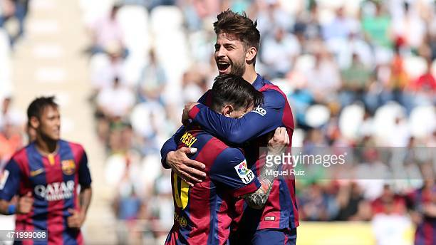 Gerard Pique of FC Barcelona celebrates with his teammate Lionel Messi as he scored the fifth goal during the La Liga match between Cordoba CF and FC...