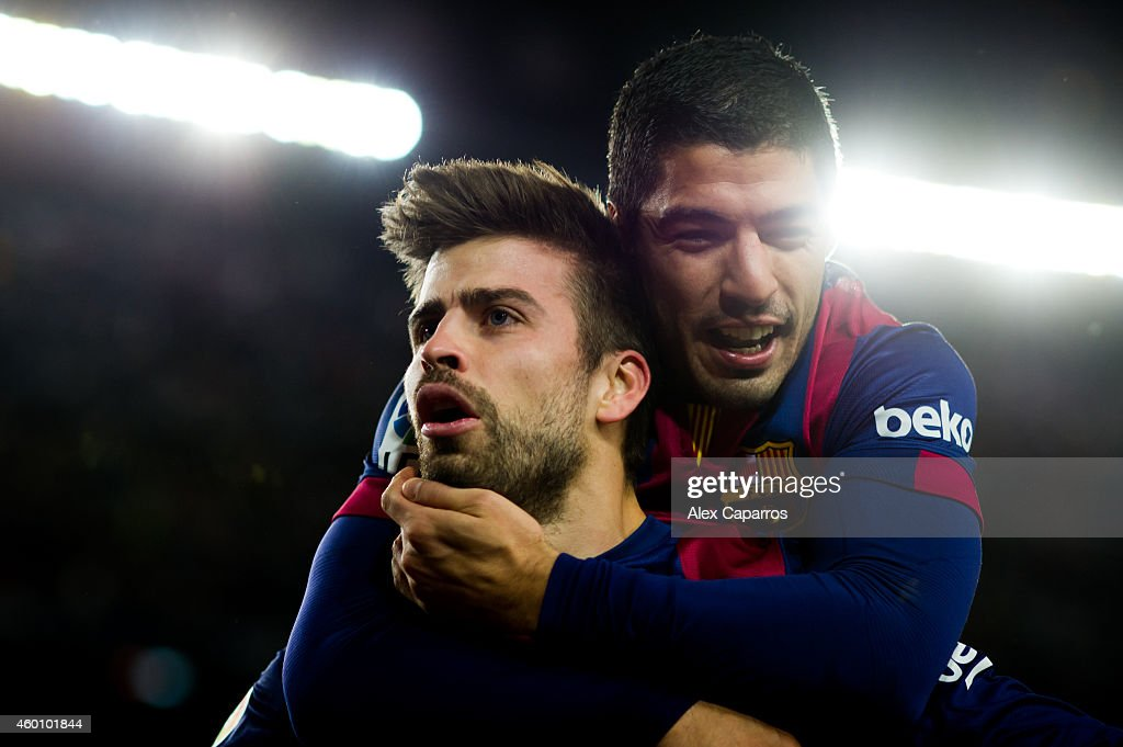 Gerard Pique (L) of FC Barcelona celebrates with his teammate Luis Suarez after scoring his team's third goal during the La Liga match between FC Barcelona and RCD Espanyol at Camp Nou on December 7, 2014 in Barcelona, Spain.