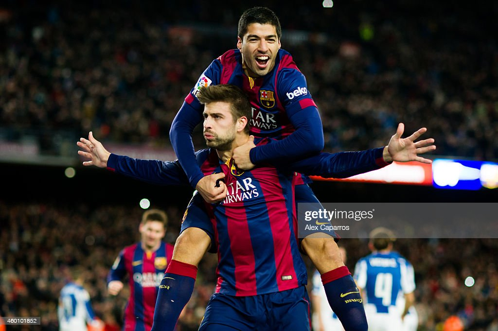 Gerard Pique (C) of FC Barcelona celebrates with his teammate Luis Suarez after scoring his team's third goal during the La Liga match between FC Barcelona and RCD Espanyol at Camp Nou on December 7, 2014 in Barcelona, Spain.