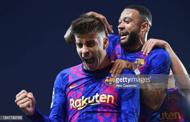 Gerard Pique of FC Barcelona celebrates with teammate Memphis Depay after scoring their team's first goal during the UEFA Champions League group E...