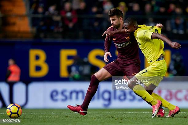 Gerard Pique of FC Barcelona competes for the ball with Cedric Bakambu of Villarreal Cduring the La Liga game between Villarreal CF and FC Barcelona...