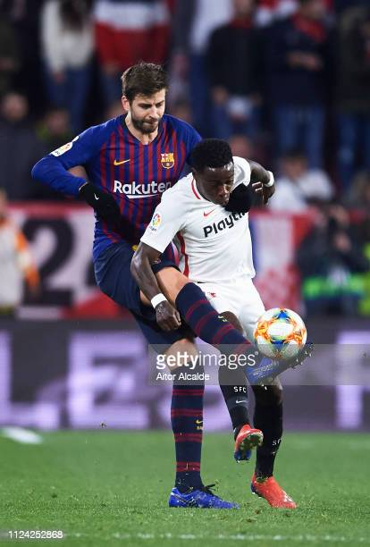 Gerard Pique of FC Barcelona competes for the ball with Quincy Promes of Sevilla FC during the Copa del Quarter Final match between Sevilla FC and FC...