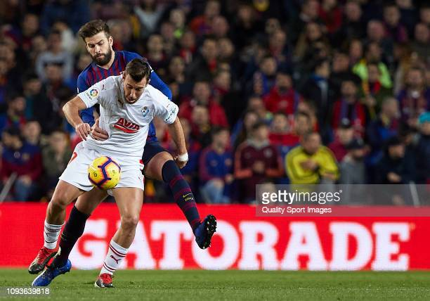 Gerard Pique of FC Barcelona competes for the ball with Sergi Enrich of SD Eibar during the La Liga match between FC Barcelona and SD Eibar at Camp...