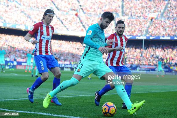 Gerard Pique of FC Barcelona controls the ball while being challenged by Koke and Felipe Luis of Club Atletico de Madrid during the La Liga match...