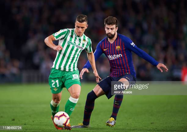 Gerard Pique of FC Barcelona duels for the ball with Giovani Lo Celso of Real Betis Balompie during the La Liga match between Real Betis Balompie and...