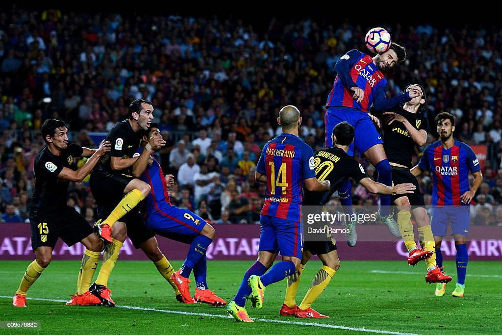 Gerard Pique of FC Barcelona heads the ball towards goal during the La Liga match between FC Barcelona and Club Atletico de Madrid at the Camp Nou stadium on September 21, 2016 in Barcelona, Spain.