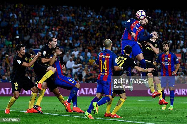 Gerard Pique of FC Barcelona heads the ball towards goal during the La Liga match between FC Barcelona and Club Atletico de Madrid at the Camp Nou...