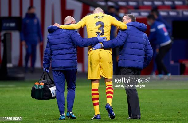 Gerard Pique of FC Barcelona leaves the game in the second half with an injury during the La Liga Santander match between Atletico de Madrid and FC...