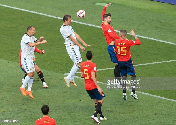 Gerard Pique of Spain gives away a penalty after a header from Artem Dzyuba of Russia connects with his outstretched arm for hand-ball during the...