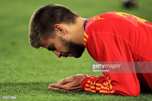 Gerard Pique of Spain lies injured with blood coming from his mouth after he was kicked in the face during the 2010 FIFA World Cup South Africa Group...