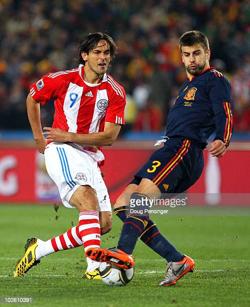 Gerard Pique of Spain tackles Roque Santa Cruz of Paraguay during the 2010 FIFA World Cup South Africa Quarter Final match between Paraguay and Spain...