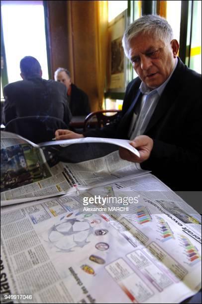 Gerard Schivardi lisant le quotidien sportif L'Equipe dans un bar