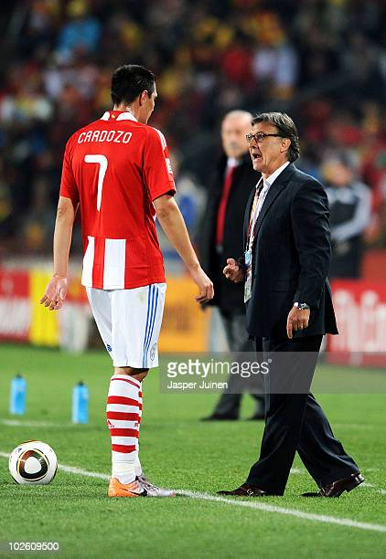Gerardo Martino head coach of Paraguay gives instructions to Oscar Cardozo during the 2010 FIFA World Cup South Africa Quarter Final match between...