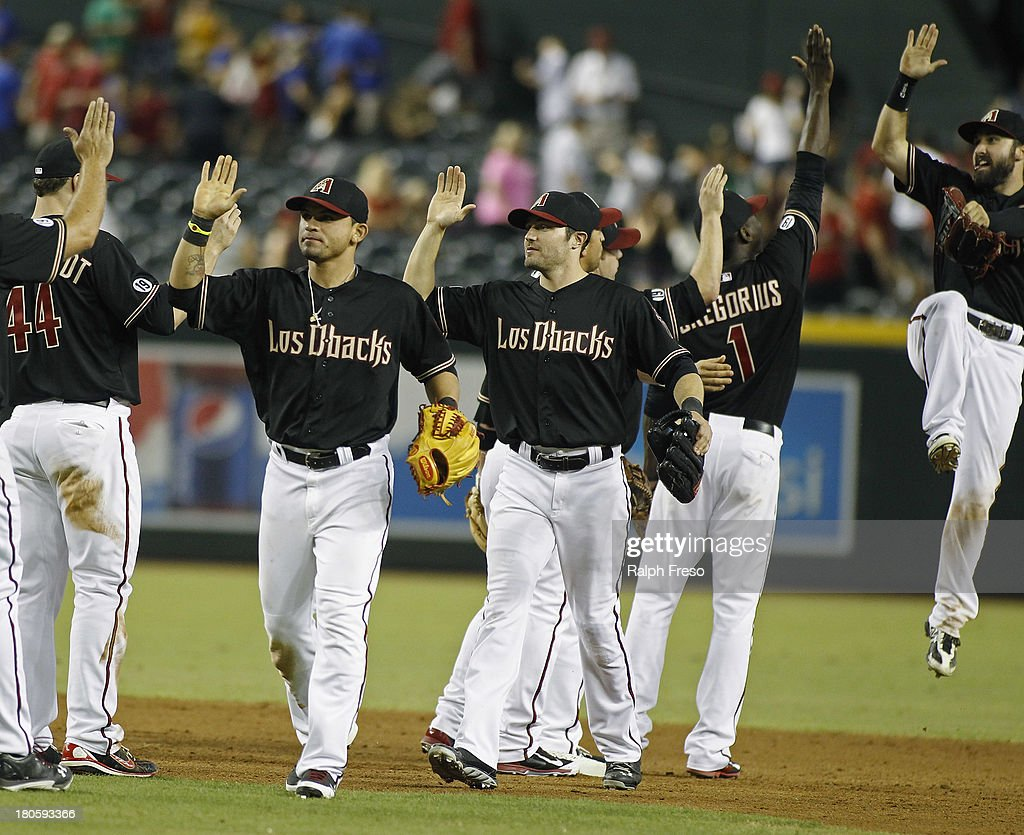 Gerardo Parra #8 and A.J. Pollock #11 of the Arizona Diamondbacks are congratulated by teammates following their 9-2 victory over the Colorado Rockies during a MLB game at Chase Field on September 14, 2013 in Phoenix, Arizona.