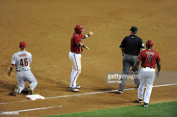 Gerardo Parra and first base coach Eric Young of the Arizona Diamondbacks argue with first base umpire Doug Eddings as Parra was tagged out by Scott...