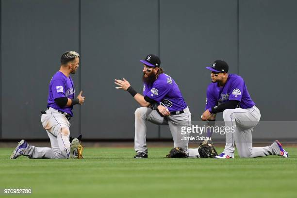 Gerardo Parra Charlie Blackmon and Carlos Gonzalez all of the Colorado Rockies talk in the outfield during a pitching change in a game against the...