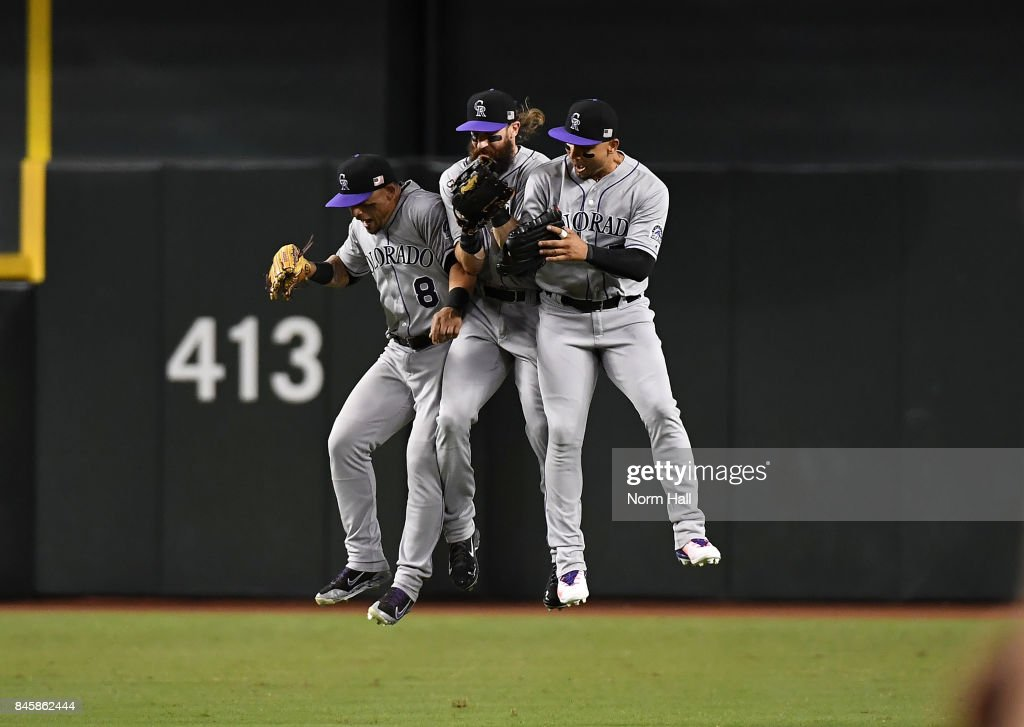 Gerardo Parra #8, Charlie Blackmon #19 and Carlos Gonzalez #5 of the Colorado Rockies celebrate a 5-4 win against the Arizona Diamondbacks at Chase Field on September 11, 2017 in Phoenix, Arizona.