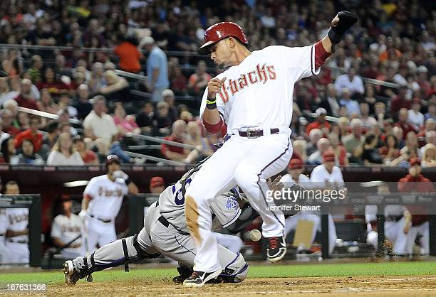 Gerardo Parra of the Arizona Diamondbacks scores as catcher Wilin Rosario of the Colorado Rockies drops the ball in the third inning at Chase Field...