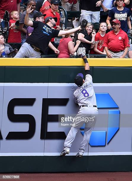 Gerardo Parra of the Colorado Rockies attempts to make a leaping catch at the right field wall on a first inning home run by Brandon Drury of the...