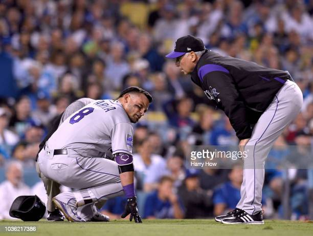 Gerardo Parra of the Colorado Rockies reacts after he was hit on the foot with a pitch from Walker Buehler of the Los Angeles Dodgers as manager Bud...