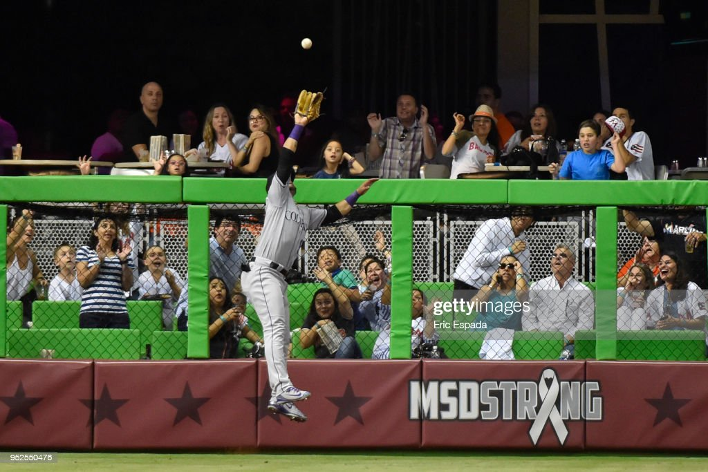 Gerardo Parra #8 of the Colorado Rockies robs J.T. Realmuto #11 of the Miami Marlins of a home run in the seventh inning of the game at Marlins Park on April 28, 2018 in Miami, Florida.