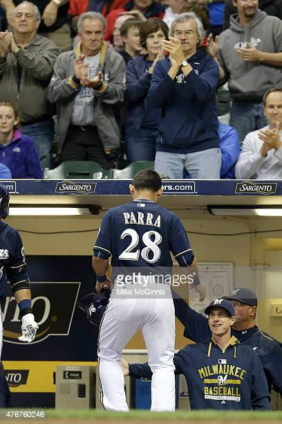 Gerardo Parra of the Milwaukee Brewers celebrates outside the dugout after reaching on a triple hit by Ryan Braun in the first inning against the...