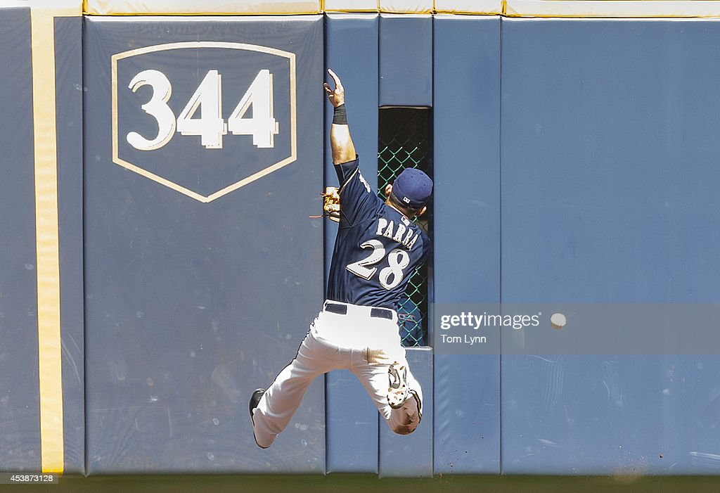 Gerardo Parra #28 of the Milwaukee Brewers tries to make a play at the wall against the Toronto Blue Jays at Miller Park on August 20, 2014 in Milwaukee, Wisconsin.