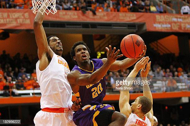 Gerardo Suero of the Albany Great Danes puts the ball up to the hoop against Fab Melo and Brandon Triche of the Syracuse Orange during the NIT Season...