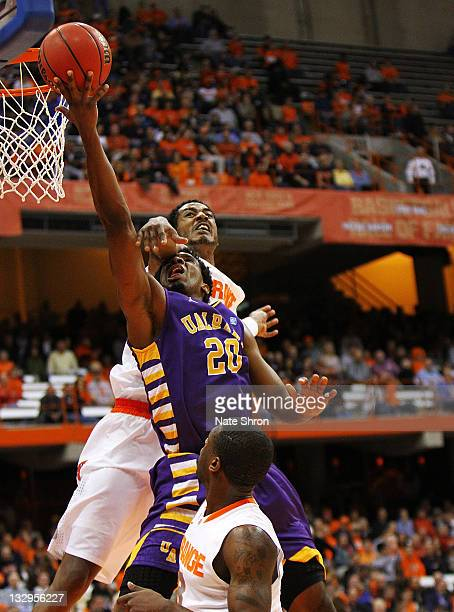 Gerardo Suero of the Albany Great Danes takes the ball to the basket as he is blocked by Fab Melo of the Syracuse Orange during the NIT Season Tipoff...