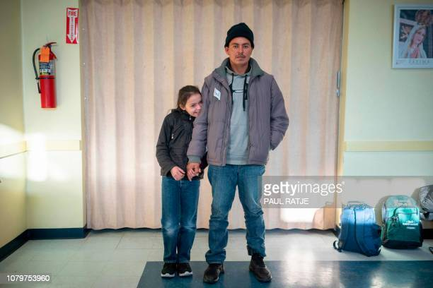 Gerbin from Santa Barbara Honduras near the border with Guatemala poses with his daughter Annarut on January 3 2019 inside the church hall of the...