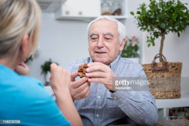 gereatric nurse doing dexterity games with elderly patient - dementia stock pictures, royalty-free photos & images