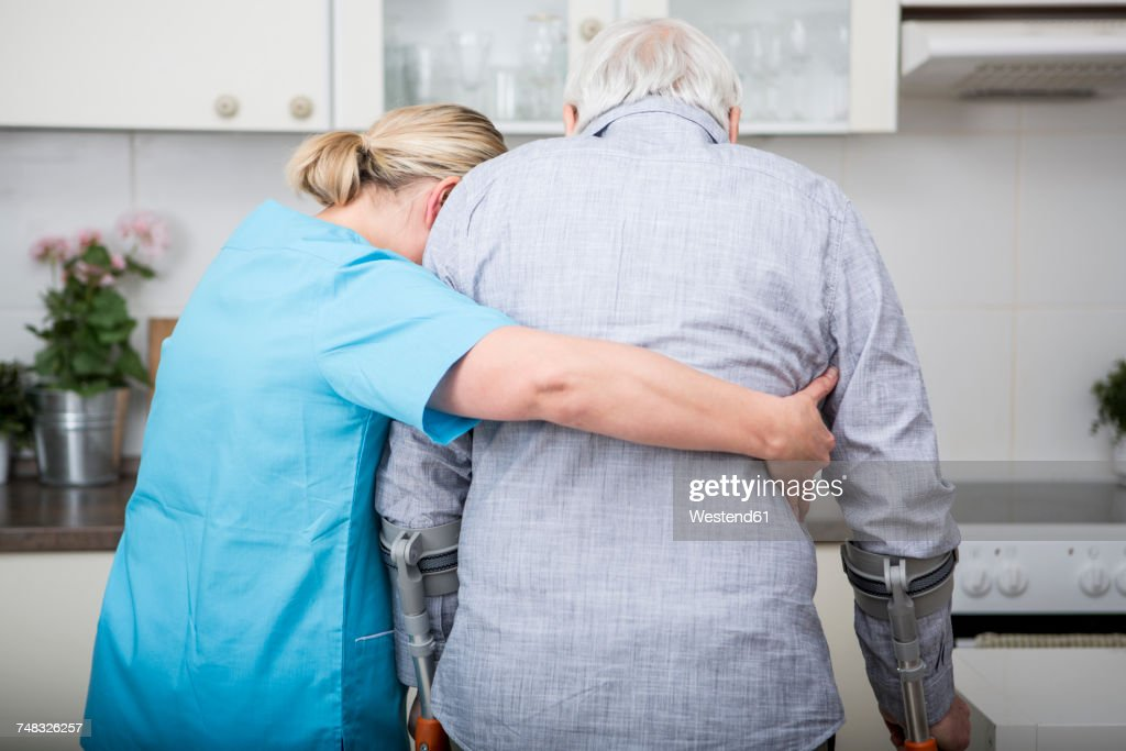 Gereatric nurse supporting week patient : Stock Photo